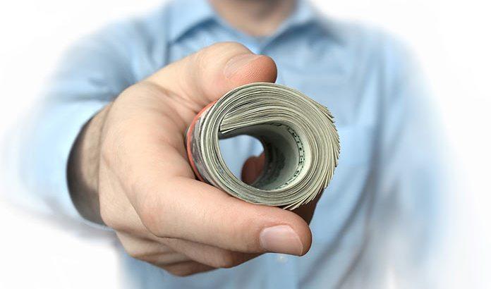 a person offering a bundle of cash