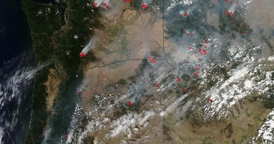 This natural-color satellite image was collected by the Moderate Resolution Imaging Spectroradiometer (MODIS) aboard the Aqua satellite on Aug. 25, 2015. Actively burning areas, detected by MODIS's thermal bands, are outlined in red. Credit NASA image courtesy Jeff Schmaltz, MODIS Rapid Response Team. Caption: NASA/Goddard, Lynn Jenner