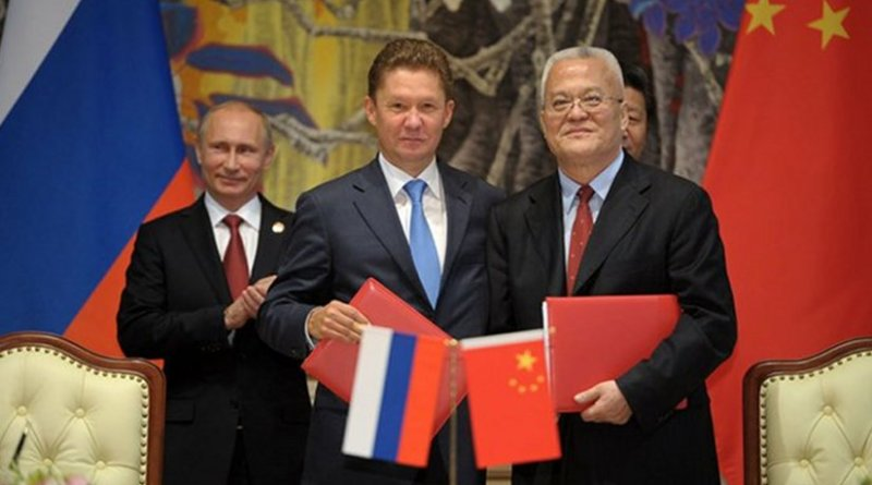 Alexey Miller on behalf of Russia and China sign a USD$ 400 billion dollar gas deal, as Vladimir Putin observes. Photo Credit: Russian presidential Website, Kremlin.ru, Wikipedia Commons.