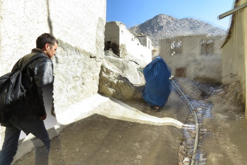 Going up the hill. The water pipe can be seen in a gulley. Zuhair's mother walks in front of Zek. Photo by Dr. Hakim.