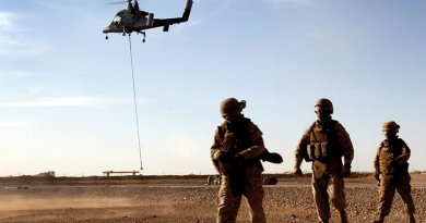 "Marines with Combat Logistics Battalion 5 return after learning about downward thrust of Kaman K1200 (""K-MAX"") unmanned helicopter during initial testing in Helmand Province, Afghanistan (U.S. Marine Corps/Lisa Tourtelot)"