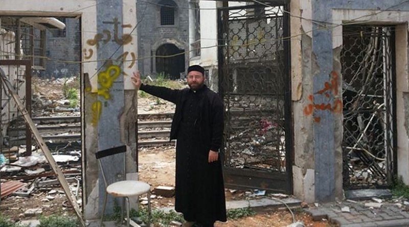 A priest stands before the ruins of St. Mary's Syriac Orthodox parish in Homs. Credit: Aid to the Church in Need.