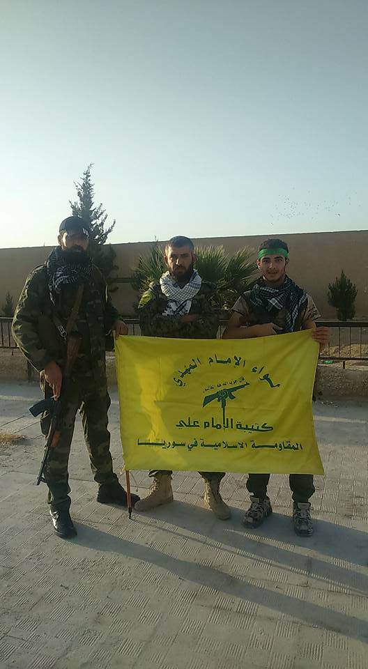 Fighters posing with the flag of Liwa al-Imam al-Mahdi (The Imam Ali Battalion). Identical with the emblem at the top of the article.