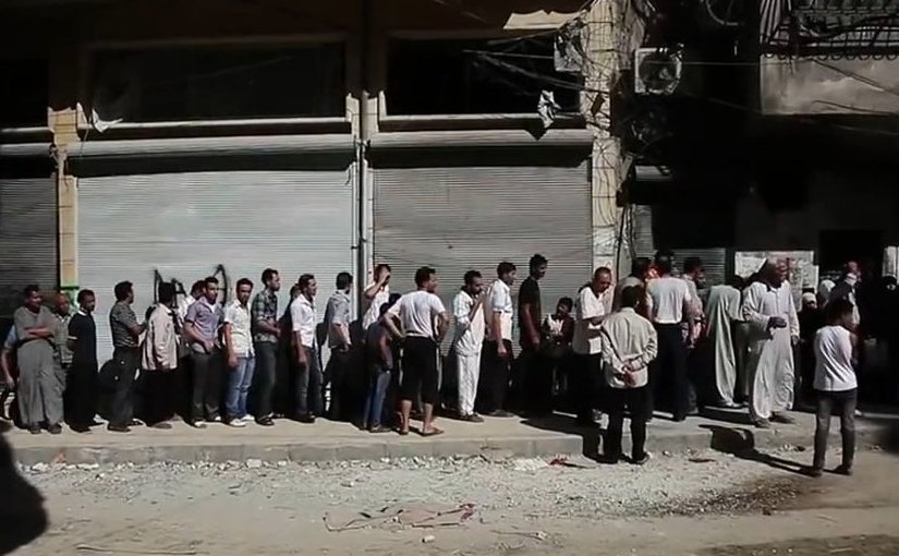 Aleppians waiting in a bread line during the Syrian civil war. File photo Voice of America News, Scott Bobb. Wikipedia Commons.