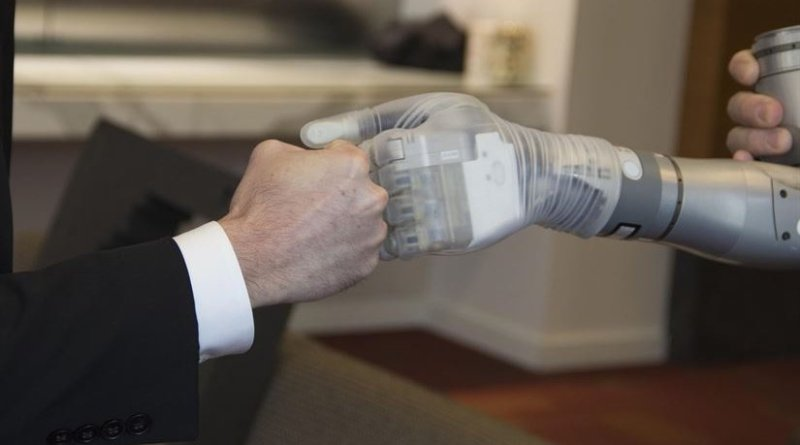 """Dr. Justin Sanchez, director of the Defense Advanced Research Projects Agency's Biological Technologies Office, fist-bumps with one of the first two advanced """"LUKE"""" arms to be delivered from a new production line during a ceremony at Walter Reed National Military Medical Center in Bethesda, Md., Dec. 22, 2016 DoD photo"""