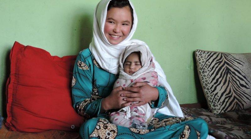 Jamila, age 11, holds a neighbor's newborn. Photo by Henrietta Cullinan.