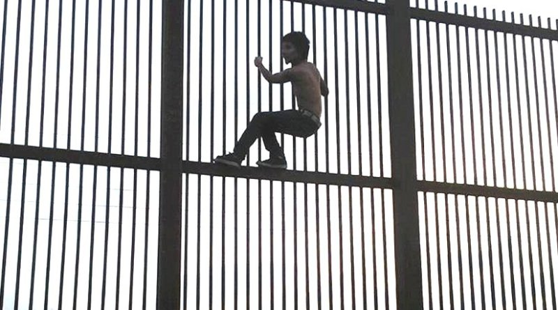 Climbing the Mexico–United States barrier fence in Brownsville, Texas. Photo by Nofx221984, Wikipedia Commons.