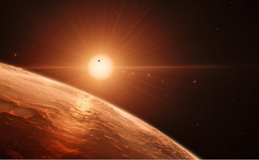 This artist's impression shows the view from the surface of one of the planets in the TRAPPIST-1 system. At least seven planets orbit this ultra cool dwarf star 40 light-years from Earth and they are all roughly the same size as the Earth. They are at the right distances from their star for liquid water to exist on the surfaces of several of them. Credit ESO/M. Kornmesser