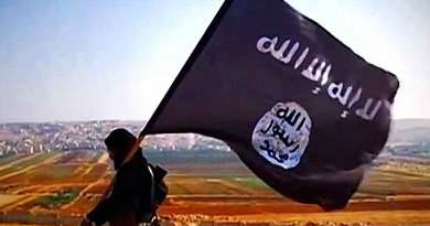 A ISIL fighter carrying the militant group's flag on Tall Dabiq which overlooks the town of Dabiq, Syria. File Photo Credit: VOA, Wikipedia Commons.