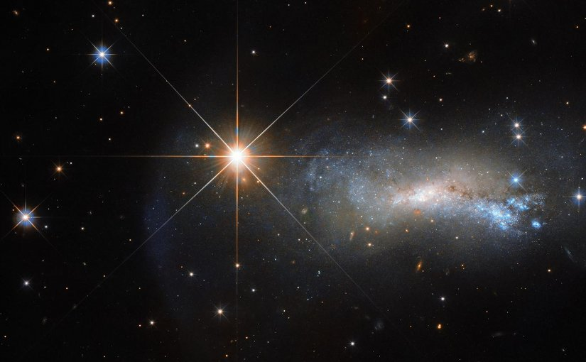 The bright object seen in this Hubble image is a single and little-studied star named TYC 3203-450-1, located in the constellation of Lacerta (The Lizard). The star is much closer than the much more distant galaxy. Credit NASA/ Hubble ESA