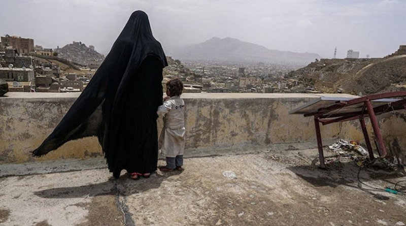 An internally displaced woman and her daughter look over the city of Sana'a, Yemen, from the roof of this dilapidated building they call their new home. Photo: Giles Clarke/UN OCHA