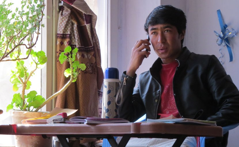 Ghulam at his study desk in Kabul, calling to make sure his family members were well, in the minutes following a bomb blast nearby