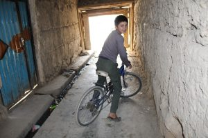 Inaam on his bicycle, near his house and the scene of a suicide bomb attack. Photo Credit: Dr. Hakim Young.