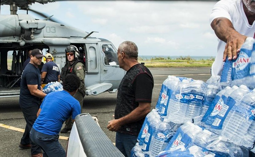 Sailors and emergency assistance responders transfer supplies off an MH-60S Seahawk helicopter in Villecas, Puerto Rico. The sailors are assigned to the USS Wasp, which is assisting with relief efforts following Hurricane Maria. Navy photo by Petty Officer 3rd Class Levingston Lewis