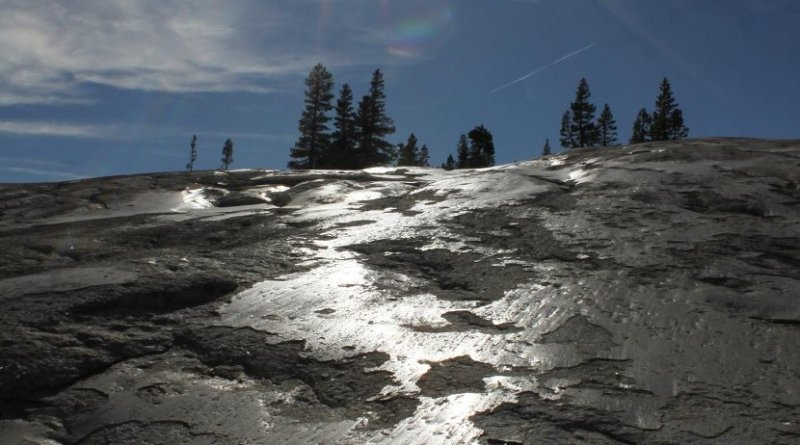 Glacial polish reflects sunlight at Pothole Dome in Yosemite National Park, California. The granitic bedrock here was polished by glacier sliding during the Last Glacial Maximum. UCSC researchers found that glacial polish forms by the accretion of a thin coating layer on top of glacially abraded surfaces. Credit Shalev Siman-Tov