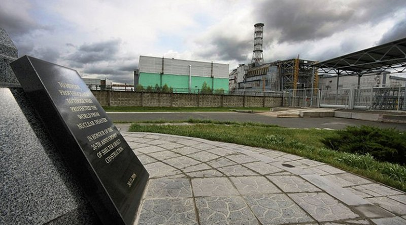 Chernobyl Nuclear Power Plant reactor number 4, the enclosing sarcophagus and the sign in the shelter object construction memorial monument. Photo by Matti Paavonen, Wikipedia Commons.