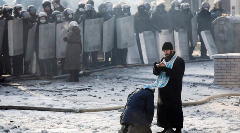 A man kneels before an Orthodox priest in an area separating police and anti-government forces in Ukraine.