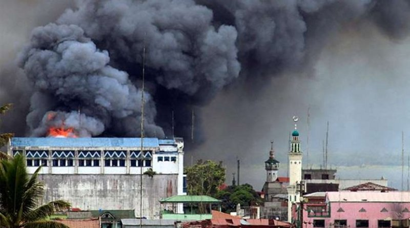 A building in Marawi is set ablaze by airstrikes carried out by the Philippine Air Force. Photo by Mark Jhomel, Wikipedia Commons.