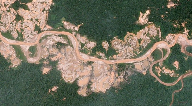 """The sprawling """"La Pampa"""" gold mine has grown quickly over the years. In 2016, however, the mine spilled south of the Malinowski River, illegally entering the Tambopata National Reserve—a protected forest. The Amazon Conservation Association used Planet data to publish a series of alerts which tracked hundreds of hectares of illegal expansion and mapped alterations to the course of the Malinowski River. The Peruvian government has intervened and is now actively targeting illegally cited mining equipment inside the reserve. Photo by Planet Labs, Inc., Wikimedia Commons."""