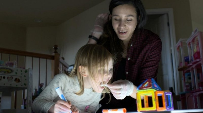 CU Boulder researcher Lameese Akacem takes a melatonin sample from preschooler Lauren Meier after exposing her to bright light before bedtime. Credit University of Colorado Boulder