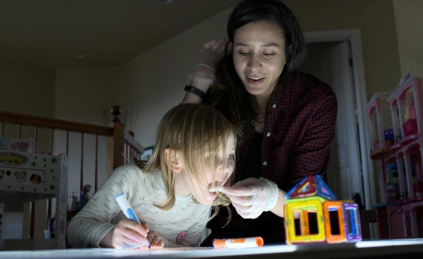 CU Boulder researcher Lameese Akacem takes a melatonin sample from preschooler Lauren Meier after exposing her to bright light before bedtime. Credit University of Colorado Boulder