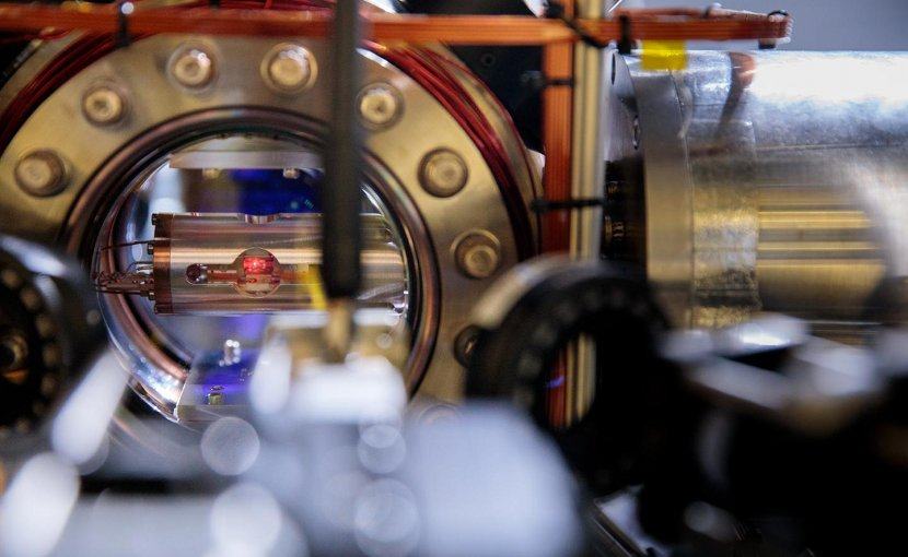 Look into the heart of an atomic clock. Here, a single atom is trapped in the metal vacuum chamber with the round window. The clock's tick comes from a laser tuned to interact with this atom. Credit Centre for Quantum Technologies, National University of Singapore
