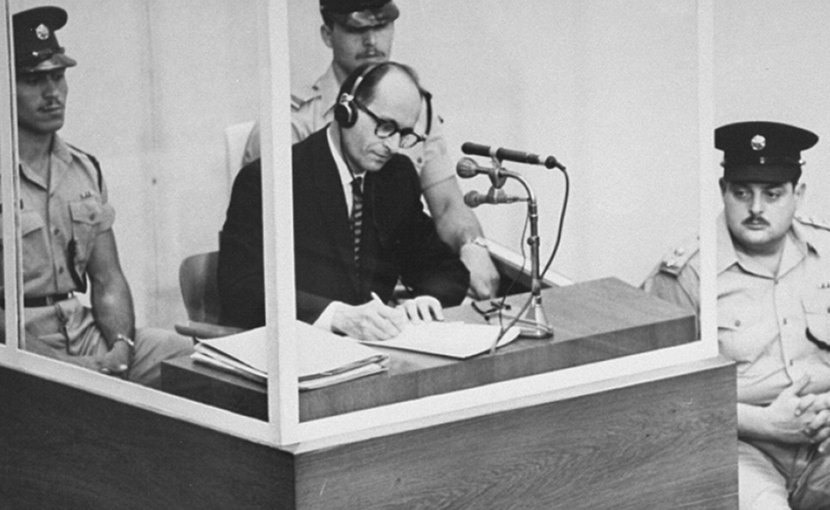 Defendant Adolf Eichmann takes notes during his trial in Jerusalem. The glass booth in which Eichmann sat was erected to protect him from assassination. (Photo credit: Israeli Government)