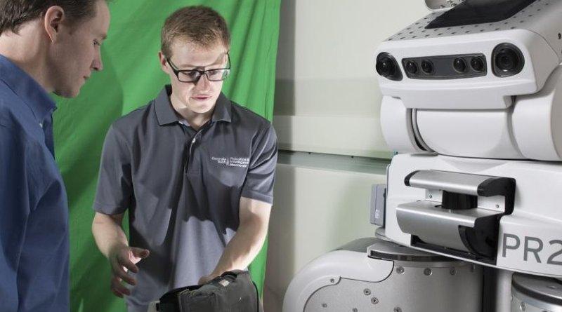 Charlie Kemp and Zackory Erickson prepare the robot. Credit Georgia Tech