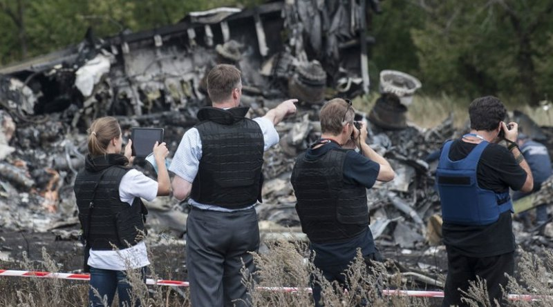 Members of the Organization for Security and Cooperation in Europe (OSCE) Special Monitoring Mission to Ukraine examine the MH17 crash site in July 2014. Photo Credit: OSCE/Evgeniy Maloletka
