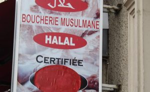 Shop sign in French and Arabic for a halal butcher's shop. Photo by Mu, Wikimedia Commons.