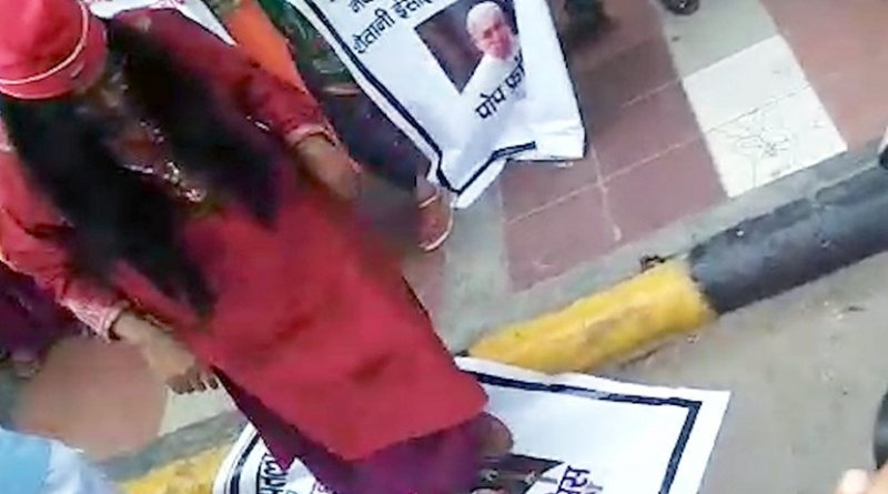 A still image of a man believed to be controversial Hindu leader Om Swami Maharaj stomping on a picture of Pope Francis. (YouTube screengrab)