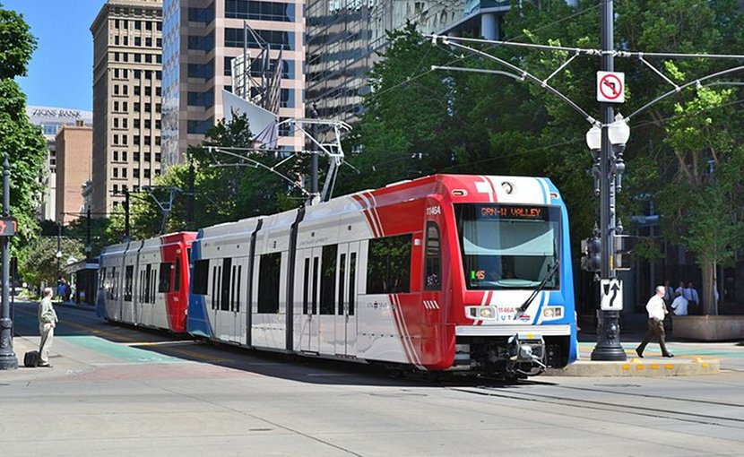A Utah Transit Authority Trax light rail vehicle traveling south on the green line in downtown Salt Lake City. Photo by Garrett, Wikimedia Commons.
