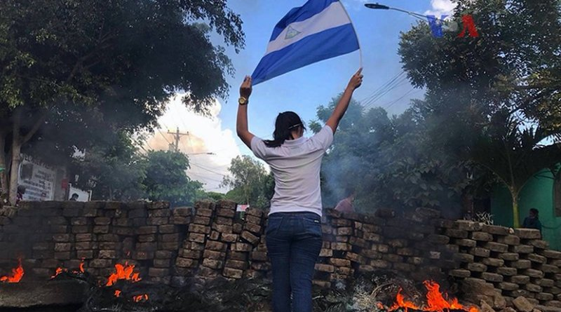 A woman stands near a burning barricade holding the national flag of Nicaragua. Photo Credit: VOA
