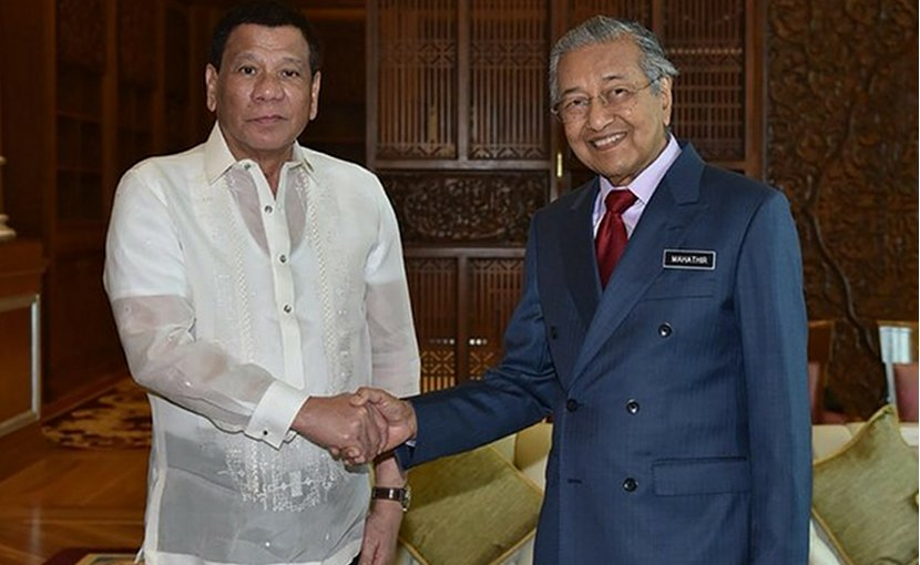 Malaysia Prime Minister Mahathir Mohamad (right), shakes hands with Philippine President Rodrigo Duterte during their meeting in Putrajaya, July 16, 2018. Malaysian Department of Information/