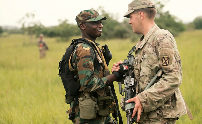 A Ghanaian soldier greets a U.S. soldier from the 1st Battalion, 32nd Infantry Regiment, during a field training exercise for the United Accord exercise at the Bundase Training Camp in Ghana, July 16, 2018. United Accord 2018 is hosted by the Ghanaian armed forces and U.S. Army Africa and consists of four combined, joint components: a command post exercise, field training exercise, jungle warfare school and medical readiness training exercise. Navy Photo by Petty Officer 2nd Class Douglas Parker