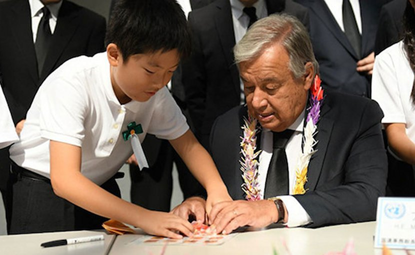 Secretary-General António Guterres folds origami cranes with young Japanese leaders at the Nagasaki Peace Memorial. Credit: Dan Powell | UN Photo.