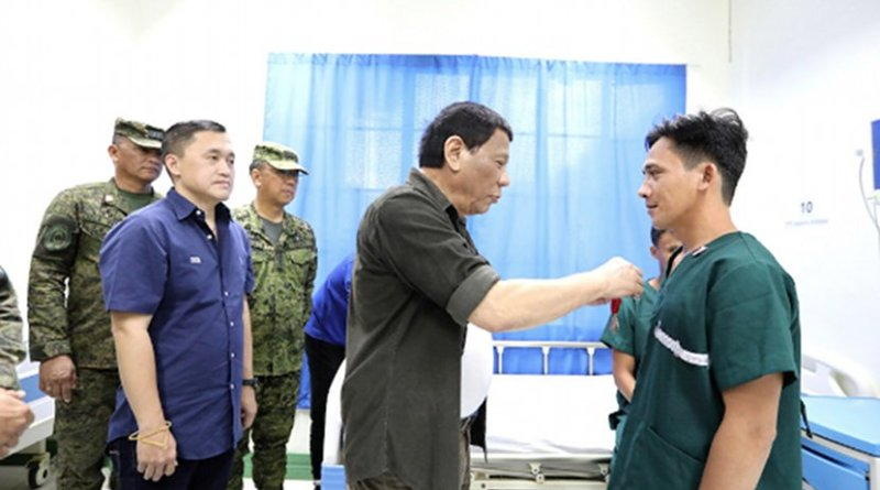 Philippine President Rodrigo Duterte pins a medal on a wounded soldier in Sulu province on Sept. 24. The president visited the soldiers who were wounded during a reported clash with alleged members of the Abu Sayyaf group on Sept. 14. (Photo courtesy of the Presidential Communications Office)