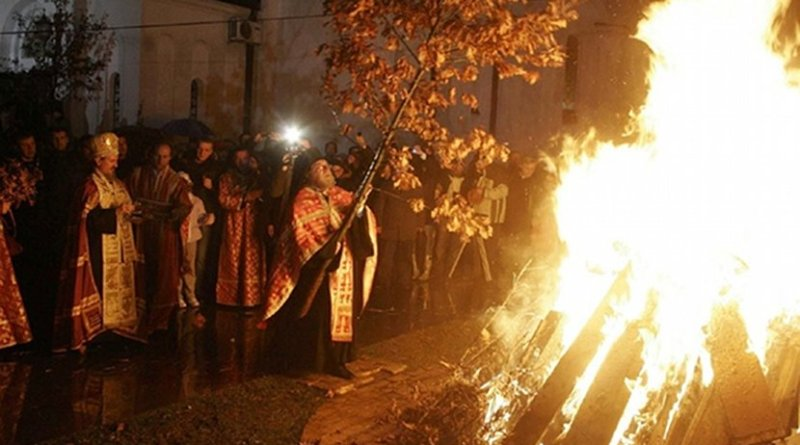 A Serbian Orthodox priest places the badnjak on a fire during a Christmas Eve celebration at the Cathedral of Saint Sava in Belgrade. Photo Credit: Lazar, Wikipedia Commons.