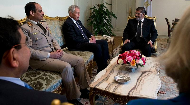 Egypt's then President Mohamed Morsi (right) and General al-Sisi (left) listen to visiting U.S. Secretary of Defense Chuck Hagel in 2013. Photo Credit: US Secretary of Defense