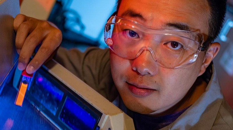 Rice University graduate student Bo Jiang shows a fluorescing vial of soluble amyloid beta peptide aggregates implicated in the onset of Alzheimer's disease. The peptides are tagged and tracked with a ruthenium complex developed at Rice that can monitor them in lab experiments as they grow over time. Credit Jeff Fitlow/Rice University
