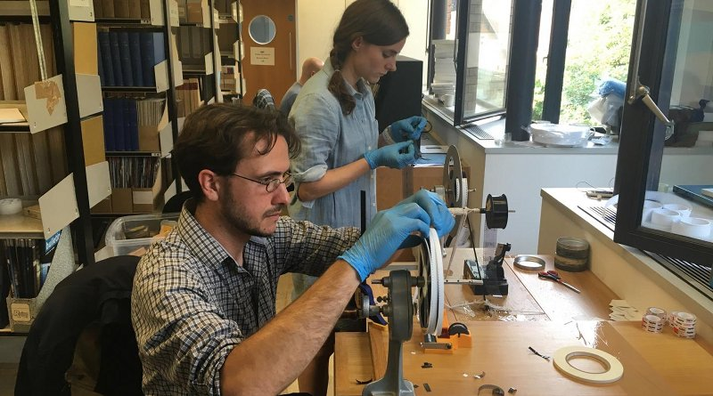 Professor Dustin Schroeder (foreground) and art historian Jessica Daniel splice 50-year-old film containing radar measurements of Antarctica into a reel in preparation for digital scanning at the Scott Polar Research Institute in the UK. Credit Courtesy of Dustin Schroeder