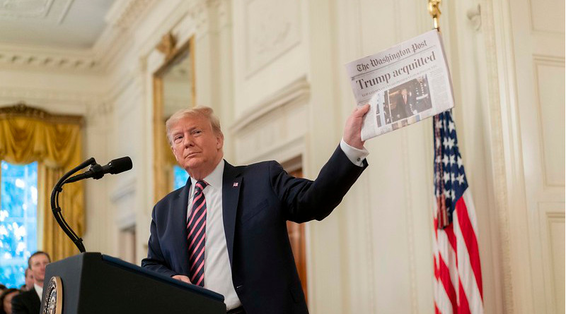President Donald J. Trump shows a newspaper headline during his address Thursday, Feb. 6, 2020 in the East Room of the White House, in response to being acquitted in the U.S. Senate Impeachment Trial. (Official White House Photo by D. Myles Cullen)