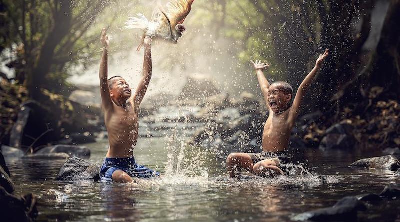 Happy children splashing water. Source: Wikimedia Commons.