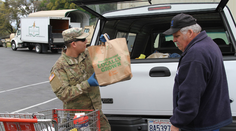 Sgt. Moises Castillo of the California Army National Guard helps an Amador County resident load food supplies into a vehicle at the Interfaith Food Bank in Jackson, Calif., March 23, 2020. Photo Credit: Army National Guard Staff Sgt. Eddie Siguenza