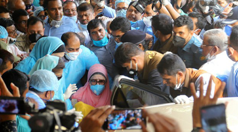 Bangladeshi opposition leader Khaleda Zia (wearing a mask and pink head covering) is wheeled to her car as she leaves the Bangabandhu Sheikh Mujib Medical University Hospital in Dhaka following her release from custody, March 25, 2020. Photo Credit: BenarNews