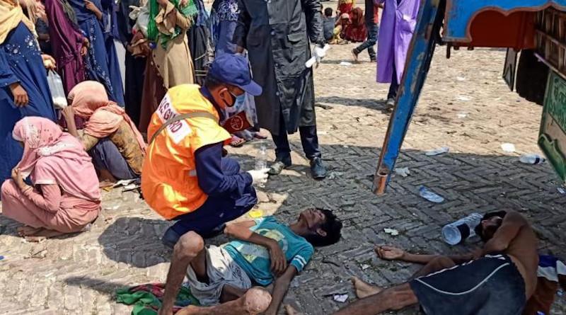 A screenshot of an exhausted Rohingya refugee receiving aid from the Bangladeshi coast guard. ©2020 Bangladeshi Coast Guard/Facebook