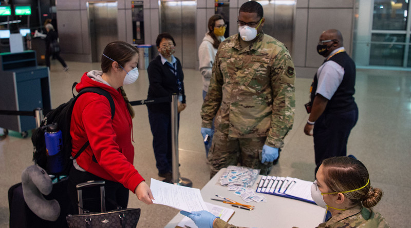 A passenger traveling to Asia hands a medical questionnaire to Air Force Airman 1st Class Nicole Mourik, a passenger service specialist with the 62nd Aerial Port Squadron at the Seattle-Tacoma International Airport in Seattle, April 30, 2020. To prevent the spread of COVID-19, passengers must answer questions about their current health, where they have traveled recently and whether they work in a medical facility. Photo Credit: Air Force Senior Airman Tryphena Mayhugh