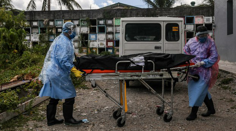 Workers wear COVID-19 protective gear as they use a stretcher to bring a body bag into the Baesa Crematorium in Quezon City, Philippines, May 5, 2020. Photo Credit: Basilio Sepe/BenarNews