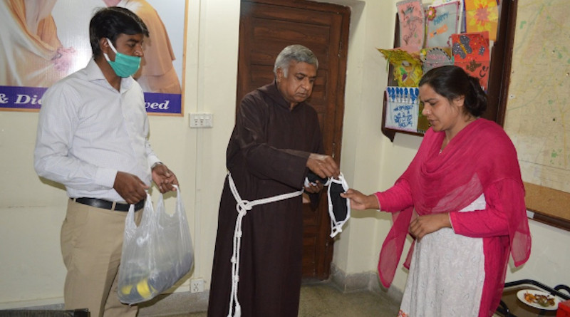 Father Francis Nadeem distributes face masks in Lahore in April. He died on July 3 at 65. (Photo: NCIDE)
