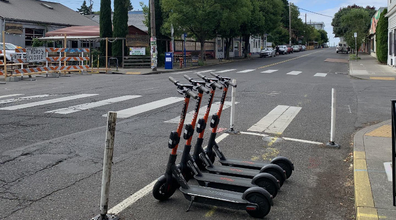 Several shared e-scooters, available for rental through a mobile app, occupy a curbside parking space that would fit a single automobile. CREDIT: Photo by Cait McCusker